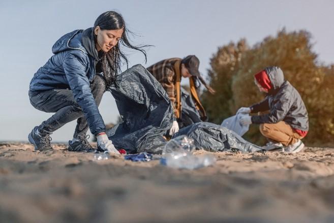 Three people picking up trash